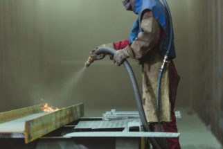 man performing abrasive blasting